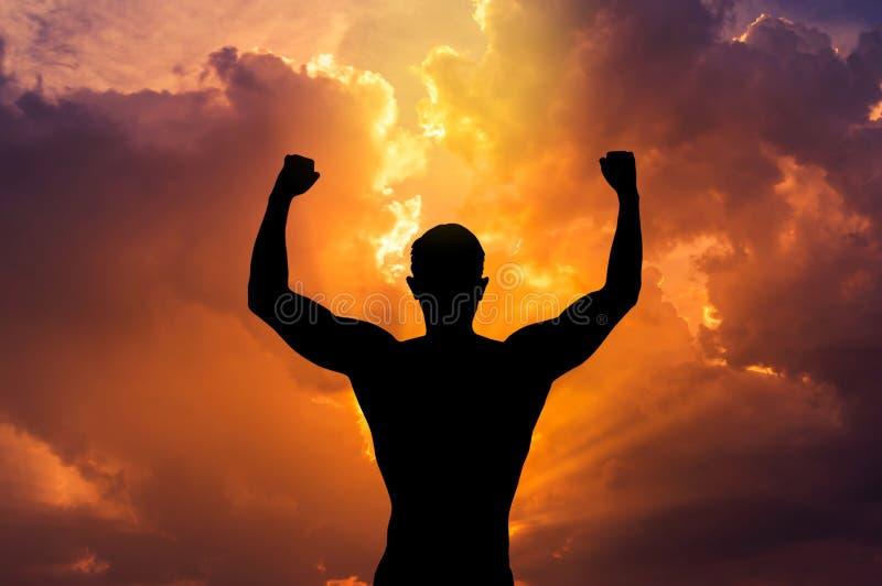 Silhouettez les bras tendus par jeune homme arrière posant le corps de forme physique sur le coucher du soleil image libre de droits