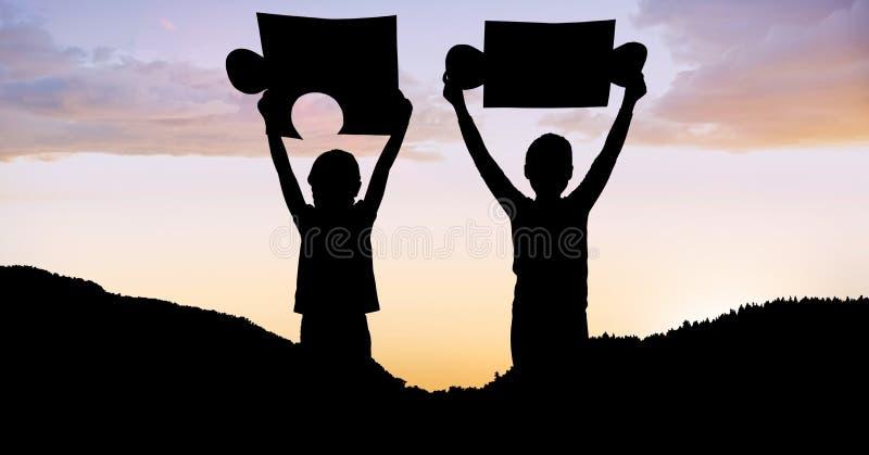 Silhouettez les enfants tenant des morceaux de puzzle sur la montagne pendant le coucher du soleil illustration libre de droits