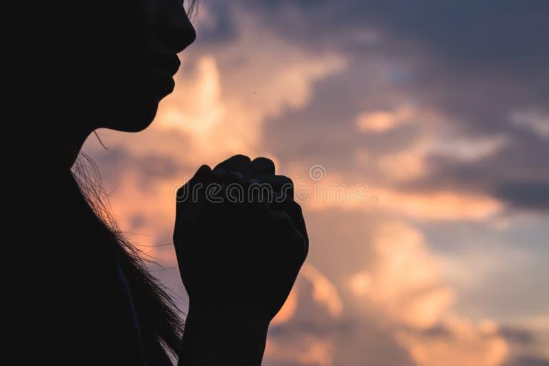 Silhouettez outre de la jeune femme priant pour des bénédictions du ` s de Dieu avec du Th image stock
