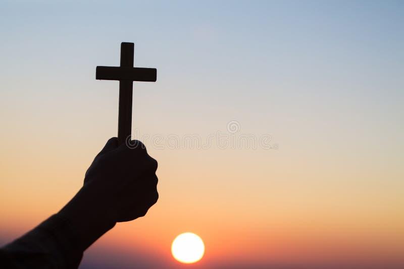 Silhouettez outre des mains tenant la croix en bois sur le fond de lever de soleil, le crucifix, symbole de la foi image libre de droits