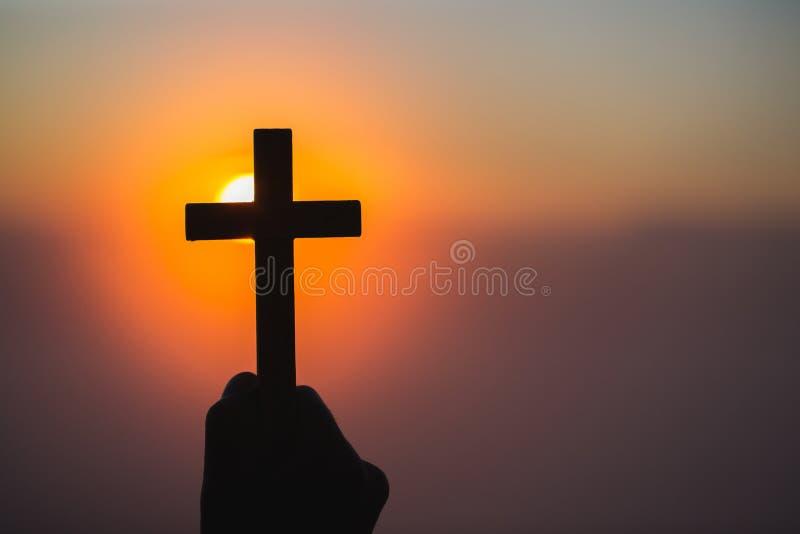 Silhouettez outre des mains tenant la croix en bois sur le fond de lever de soleil, le crucifix, symbole de la foi photo stock