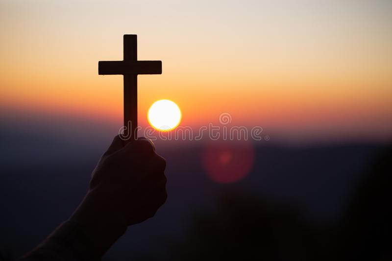 Silhouettez outre des mains tenant la croix en bois sur le fond de lever de soleil, le crucifix, symbole de la foi images libres de droits