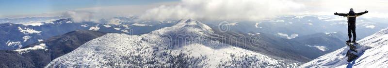 Silhouettieren Sie allein von der touristischen Stellung auf die schneebedeckte Gebirgsoberseite in der Siegerhaltung mit den ang lizenzfreies stockfoto