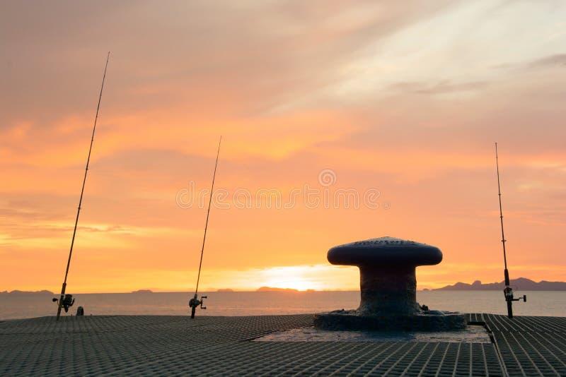 Silhouettieren Sie Angeln mit Sonnenunterganghimmel am Küstenpier lizenzfreie stockbilder