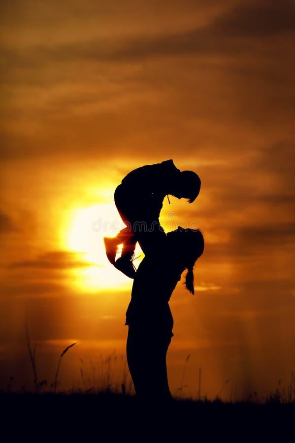 Silhouettieren Sie das Bild der Mutter spielend mit ihrem Kind stockfoto
