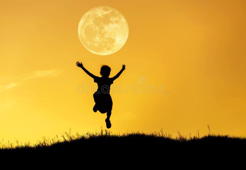 Silhouettieren Sie das kleine Mädchen, das zum Himmel auf Sonnenuntergang mit Vollmond springt lizenzfreie stockbilder