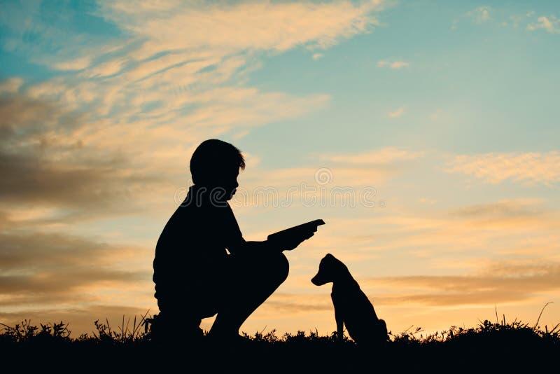 Silhouettieren Sie den Jungen, der ein Buch mit kleinem Hund liest lizenzfreie stockfotografie