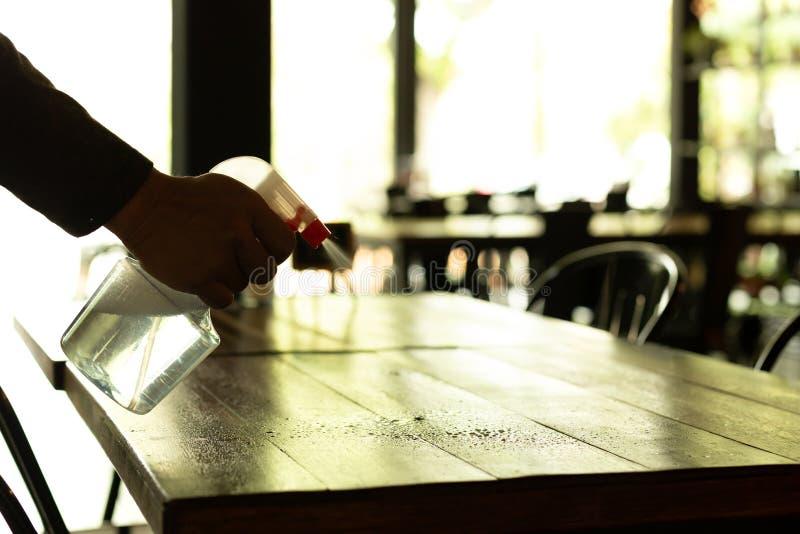 Silhouettieren Sie den Kellner, der die Tabelle mit desinfizierendem Spray in einem Restaurant säubert lizenzfreie stockfotografie