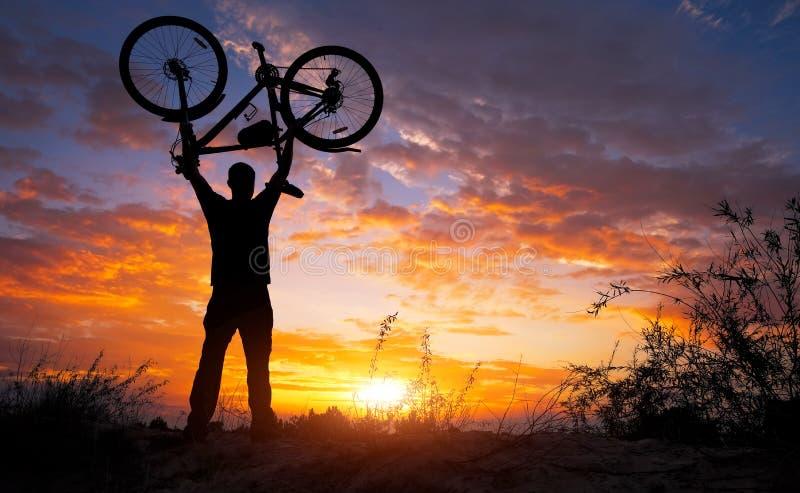 Silhouettieren Sie den Mannstand in anhebendem Fahrrad der Aktion über seinem Kopf lizenzfreies stockfoto