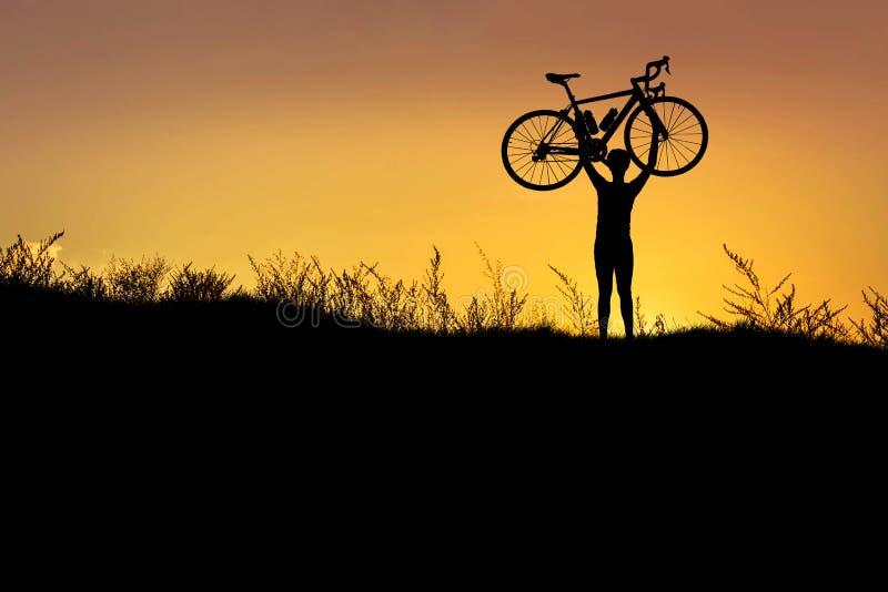 Silhouettieren Sie den Mannstand in anhebendem Fahrrad der Aktion über seinem Kopf mit Sonnenuntergang stockbild