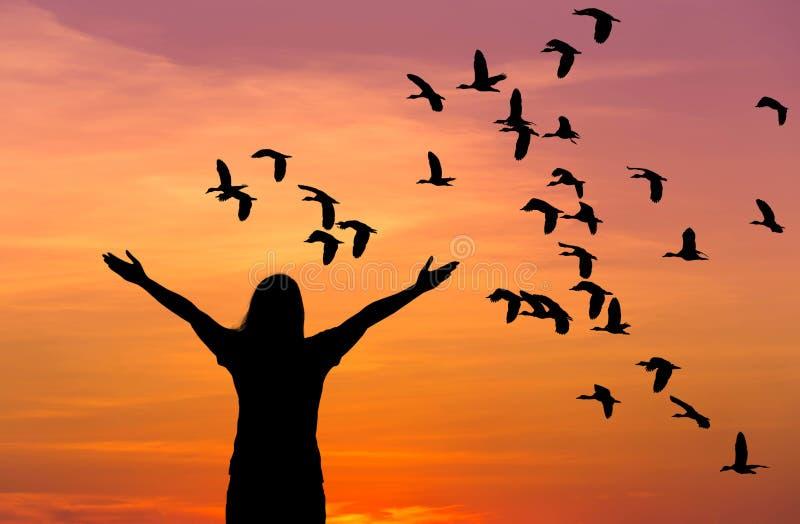 Silhouettieren Sie die Frauenstellung, die herauf Hände während der Menge wenigen pfeifenden Entenfliegens auf Sonnenuntergang an lizenzfreie stockfotografie