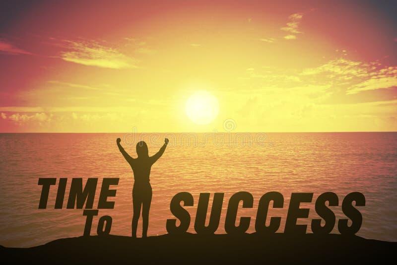 Silhouettieren Sie die junge Frau, die sich ihre Hand über Siegerkonzept rechtzeitig gegen Erfolgstext behauptet und anhebt stockbild