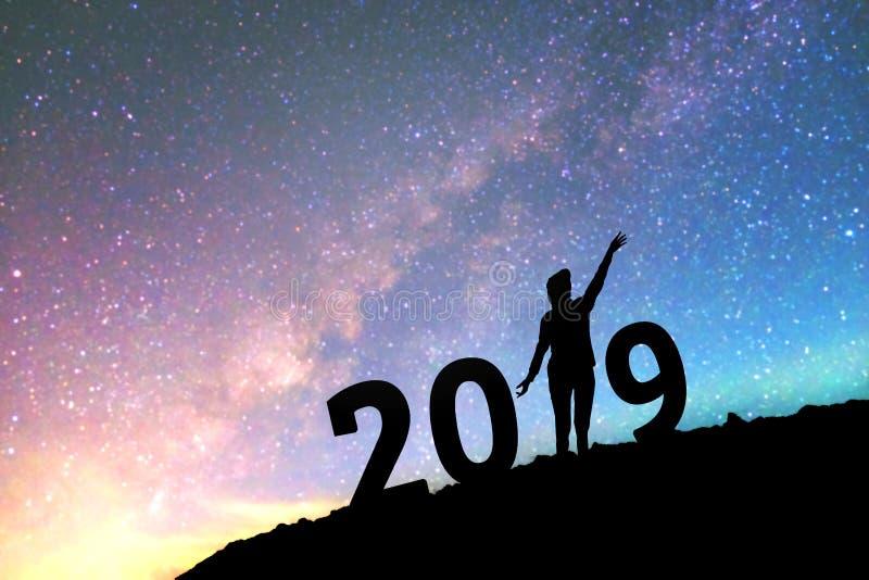 Silhouettieren Sie die junge Frau, die für Hintergrund des neuen Jahres 2019 auf Th glücklich ist lizenzfreie stockfotos