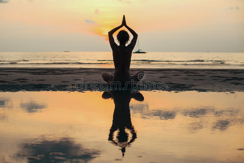 Silhouettieren Sie die Yogafrau, die am Seeufer meditiert relax stockfotos