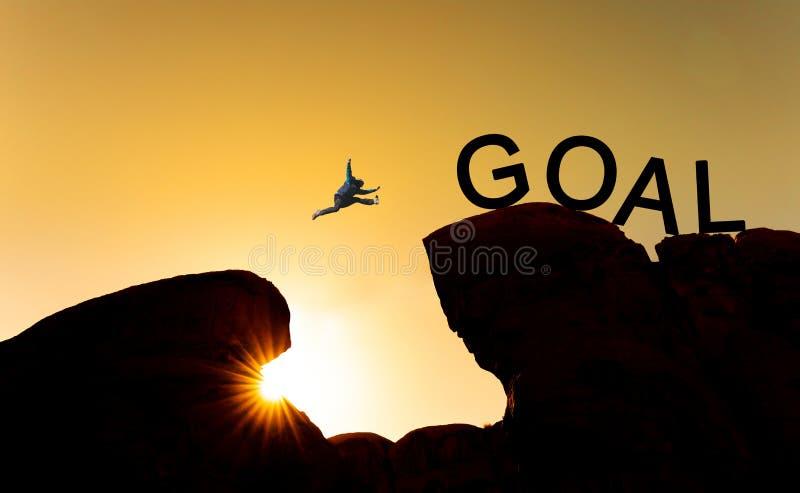 Silhouettieren Sie einen Mann, der über Abgrund zum Ziel springt Erzielen Sie Ziel, Unternehmensziele, Herausforderung und Erfolg lizenzfreie stockfotografie