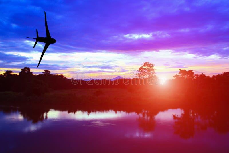 Silhouettieren Sie Flugzeug mit Sonnenunterganglicht mit Reflexfluß stockfotos