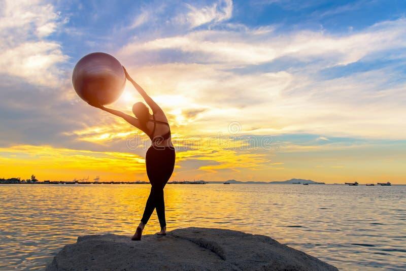 Silhouettieren Sie gesunde Frau, das Lebensstil, dentrainieren wesentlich und übender Yoga- und Turnhallenball auf dem Felsen bei lizenzfreie stockfotos