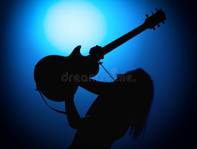 Silhouettieren Sie Gitarristen eines Rockbands mit Gitarre auf blauem Hintergrund lizenzfreie stockbilder