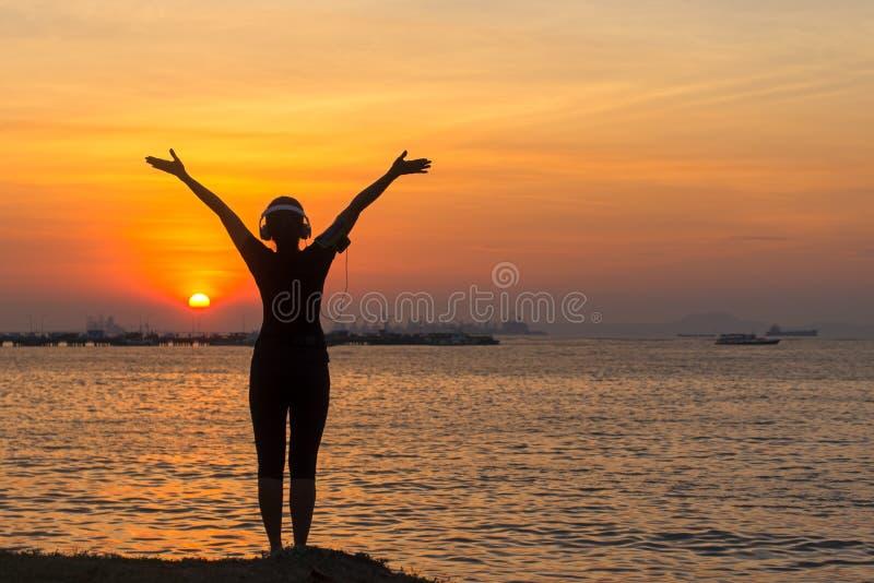 Silhouettieren Sie hörende Musik des Frauenläufers und glaubende Freiheit, glücklich und Natursonnenuntergang genießen lizenzfreies stockfoto