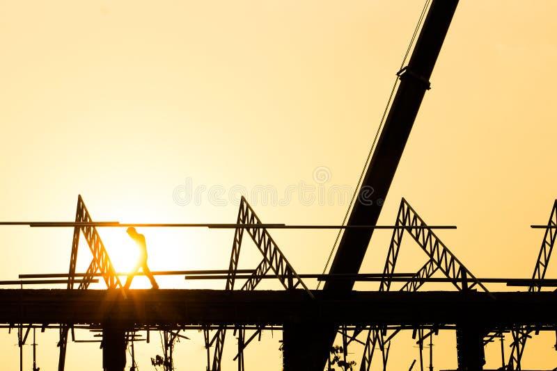 Silhouettieren Sie Ingenieurdaueraufträge, damit Baumannschaften an Schwerindustrie und Sicherheit des hohen Bodens arbeiten stockbilder