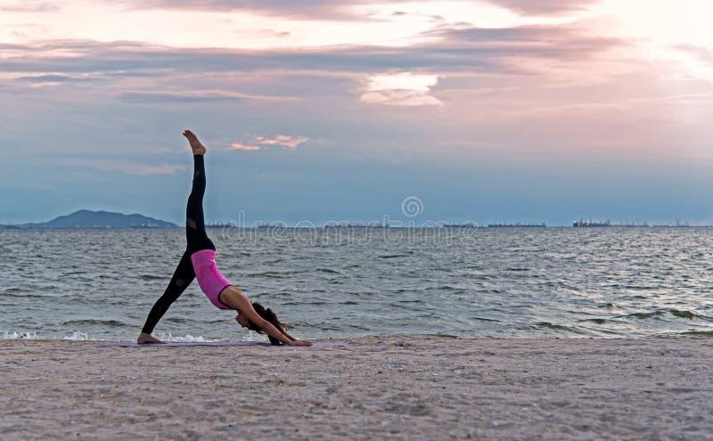 Silhouettieren Sie junge Frau, das Lebensstil, dentrainieren wesentlich und übender Yogaball auf dem Strand bei Sonnenuntergang m lizenzfreie stockbilder