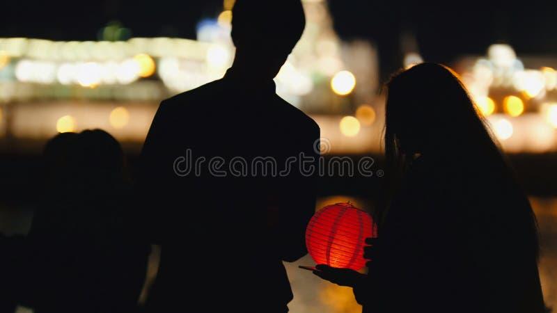 Silhouettieren Sie liebevolle Paare am Festival von sich hin- und herbewegenden Laternen nahe Fluss nachts lizenzfreie stockbilder