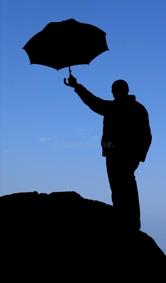 Silhouettieren Sie Mann mit Regenschirm auf dem Felsen lizenzfreies stockbild