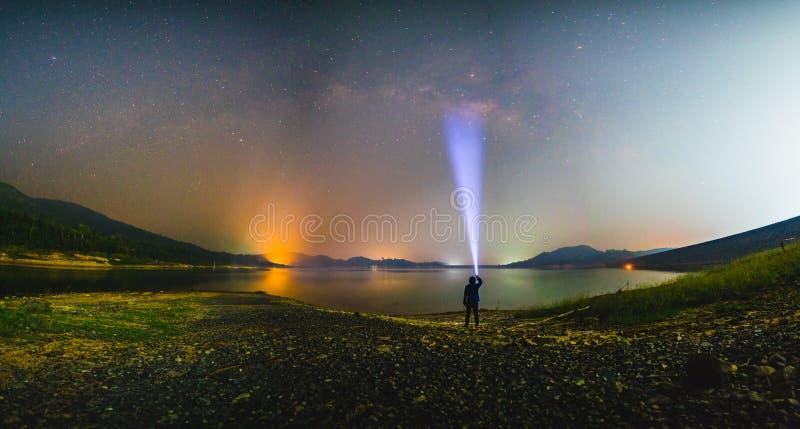 Silhouettieren Sie Mann mit Taschenlampe und Milchstraßegalaxie am See stockfoto