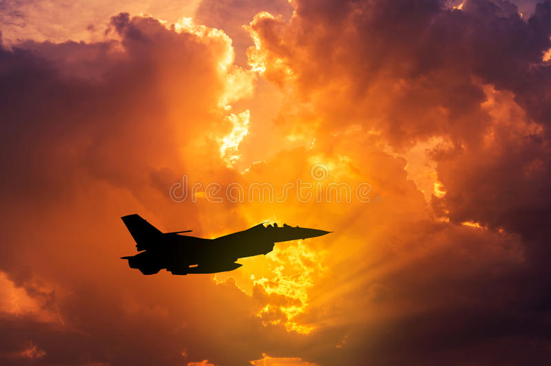 silhouettieren Sie Militärflugzeugfliegen des Falkekampfflugzeugs auf Sonnenuntergang lizenzfreies stockfoto