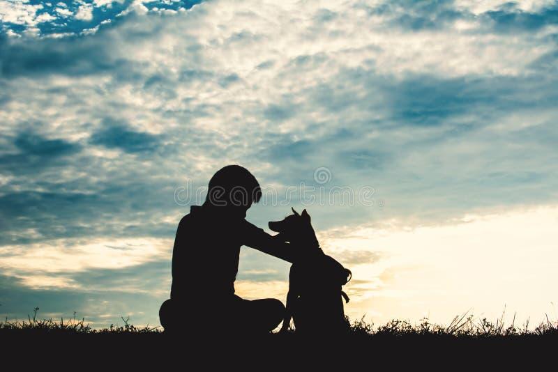 Silhouettieren Sie netten Jungen und den Hund, die bei Himmelsonnenuntergang spielt stockbild