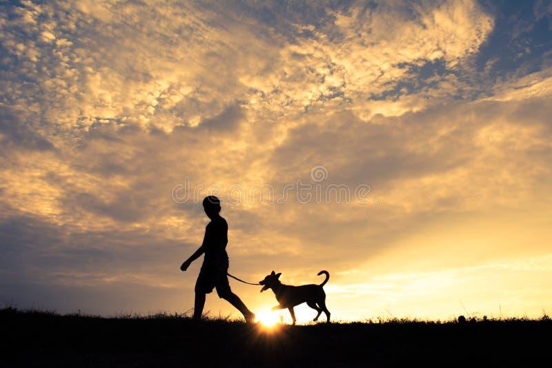 Silhouettieren Sie netten Jungen und den Hund, die bei Himmelsonnenuntergang spielt lizenzfreies stockfoto