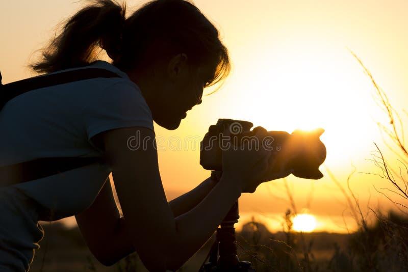 Silhouettieren Sie Porträt einer jungen Frau, die eine schöne Natur bei Sonnenuntergang auf Fotoausrüstung fotografiert lizenzfreie stockfotografie