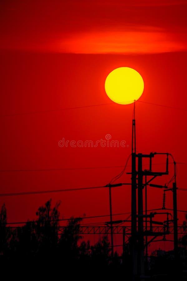 Silhouettieren Sie Sonnenuntergang in der Stadt und im elektrischen Pfosten stockbild