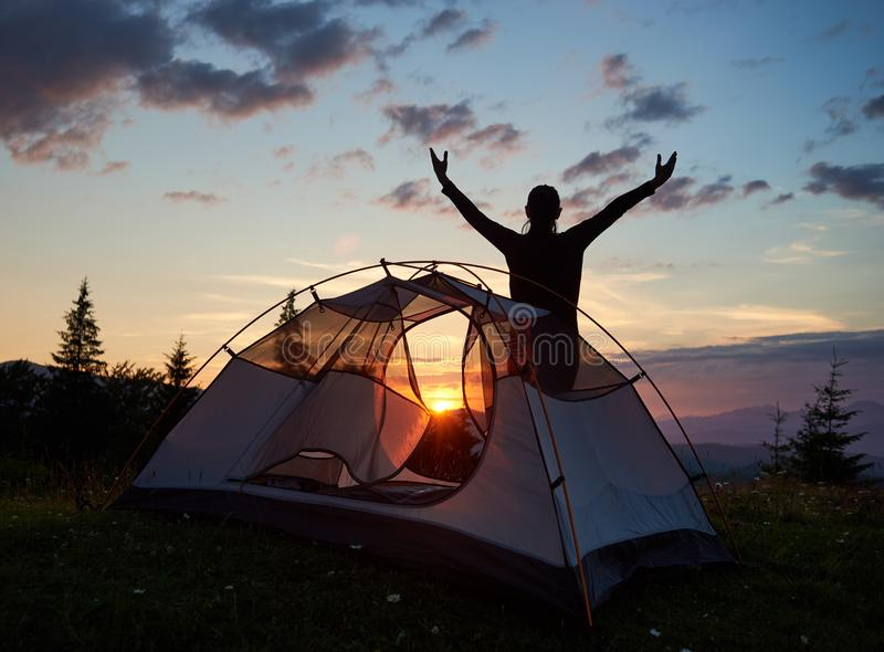Silhouettieren Sie touristische weibliche Stellung mit ihrem Hände angehobenen Himmel auf Berg nahe Campingplatz bei Sonnenaufgan lizenzfreies stockfoto