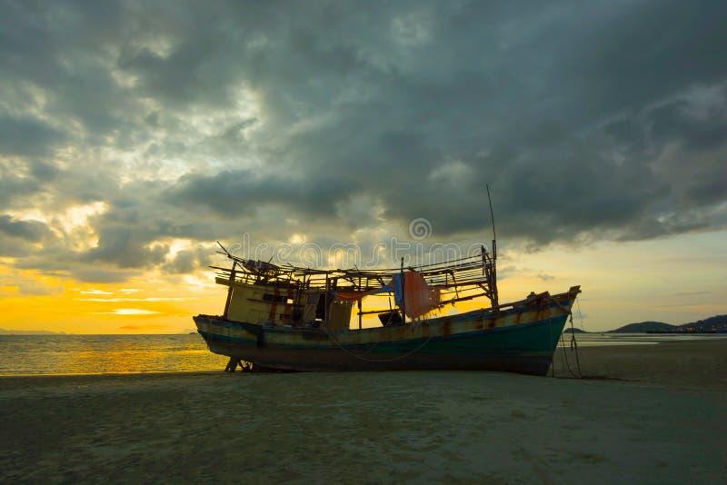 Silhouettieren Sie verlassenes Fischerboot auf der Sandbank lizenzfreie stockfotos