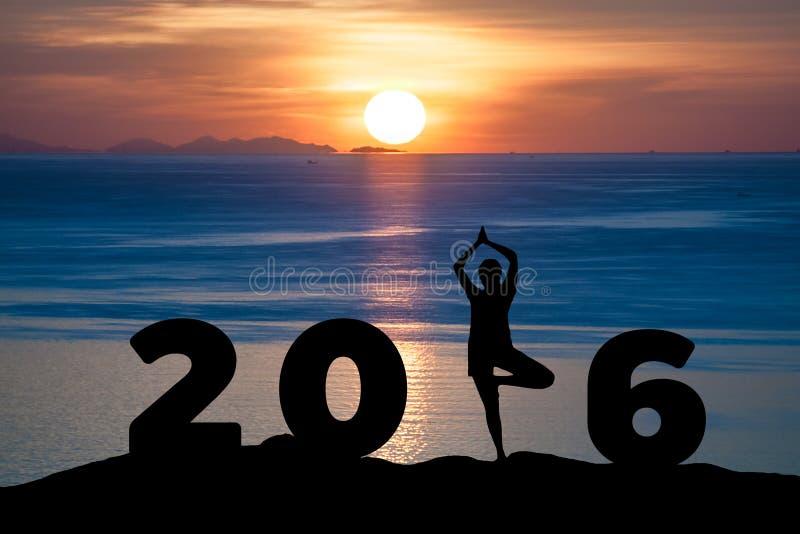 Silhouettieren Sie Yoga Spiel der jungen Frau auf dem Meer und 2016 Jahren beim Feiern des neuen Jahres lizenzfreie stockfotografie