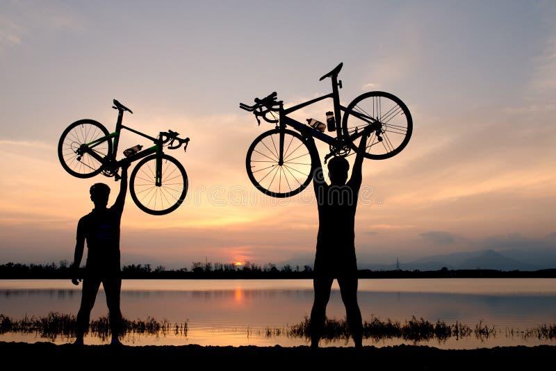 Silhouettieren Sie Zwei-mannstand in anhebendem Fahrrad der Aktion über seinem Kopf auf Sonnenuntergang lizenzfreie stockbilder