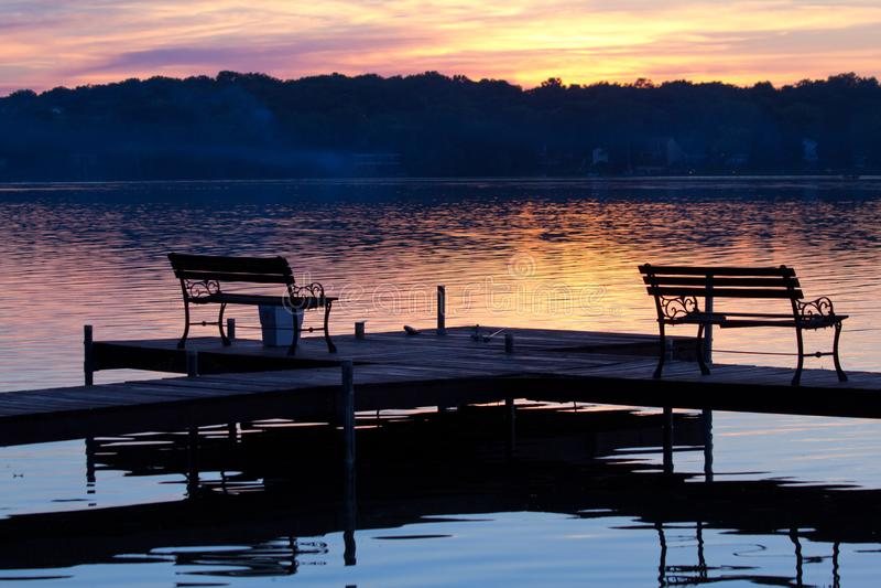 Silhouettierte Bänke auf hölzernem Pier bei Sonnenuntergang lizenzfreie stockbilder