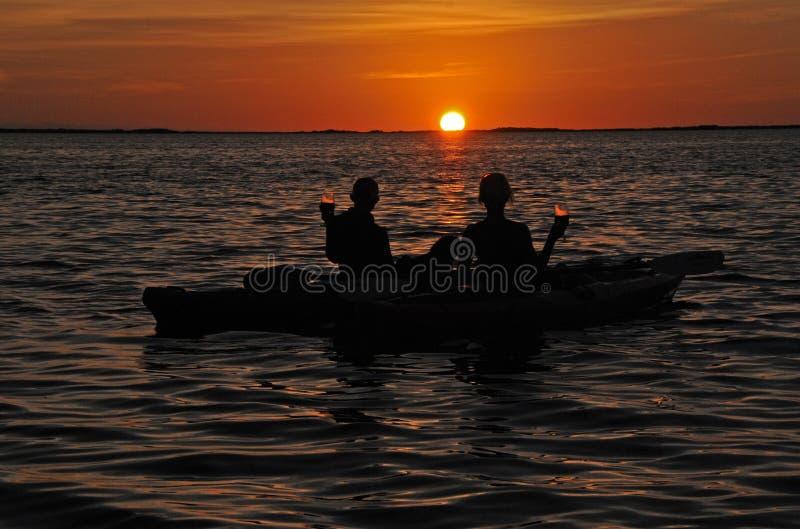 Silhouettierte Paare im Kajak bei Sonnenuntergang mit Wein lizenzfreie stockbilder