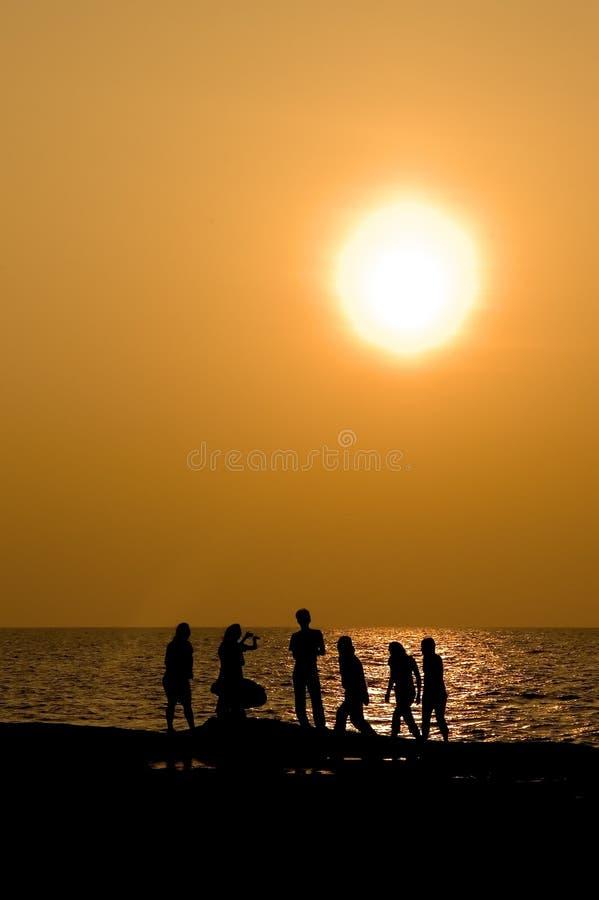 Silhouettierte Völker Am Sonnenuntergang Stockbild