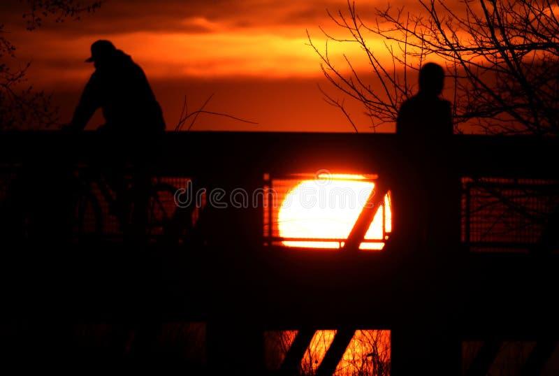 Silhouettierte Zahlen gegen einen glühenden Sonnenuntergang am Euclid-Nebenflusspark stockbild