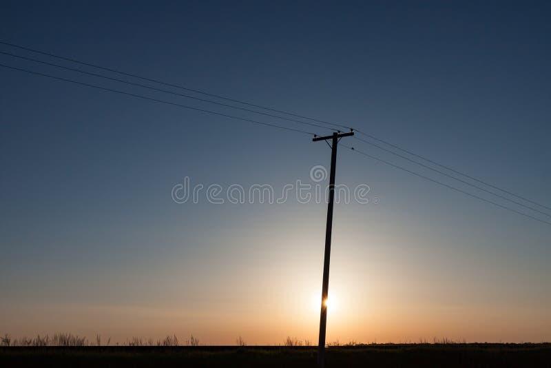 Silhouettierter Strommast auf kanadischem Grasland bei Sonnenaufgang lizenzfreie stockfotografie
