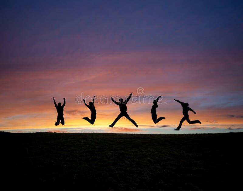 Silhouettierter Teenager, der in Sonnenuntergang springt lizenzfreies stockfoto