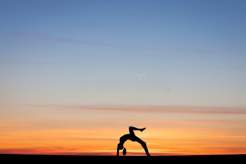 Silhouettierter Turner, der Bogen im Sonnenuntergang tut stockbilder