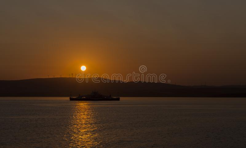 Silhouetveerboot onder het Plaatsen Zon stock foto's
