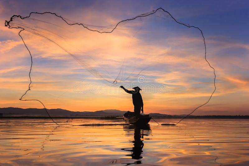 Silhouetvisser op vissersboot die met zonsopgang netto plaatsen stock foto's