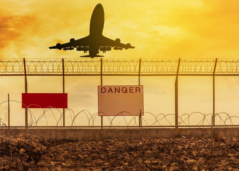 Silhouetvliegtuig het vliegen start van baan met van het het prikkeldraadmetaal van het veiligheidsscheermes de omheiningsachterg royalty-vrije stock foto's