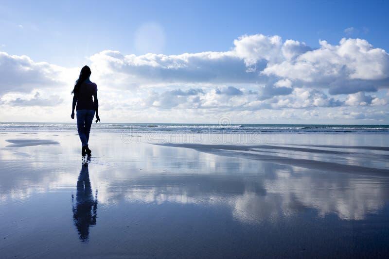 Silhouetvrouw die bij een Strand lopen stock foto's
