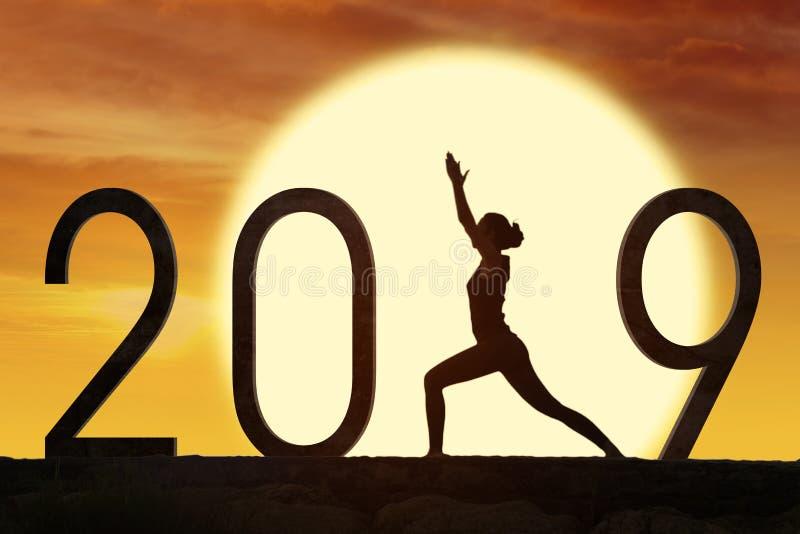 Silhouetvrouw die yoga met nummer 2019 uitoefenen stock foto's