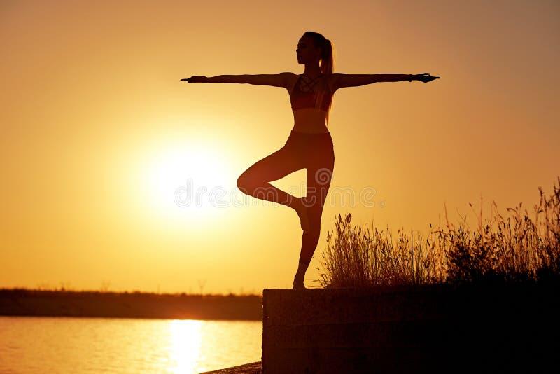 Silhouetvrouw het praktizeren yoga of het uitrekken zich op de strandpijler bij zonsondergang of zonsopgang stock foto